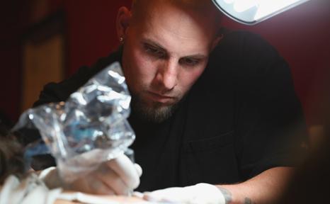 Tattoo artist Chris Peltier, carefully inks WSU student Alivia DeGagne at Blood Diamond Ink, Monday, Oct. 7, 2013.