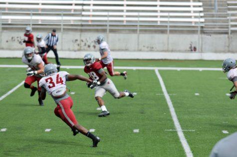 Running back Jamal Morrow carries the ball during practice at Martin Stadium, April 19.