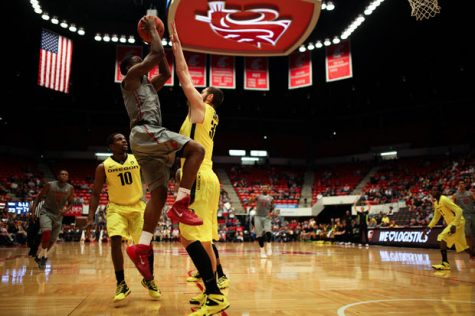 Cougar guard Ike Iroegbu attempts a contested layup against the Oregon Ducks in Beasley Coliseum, Jan. 26, 2014.