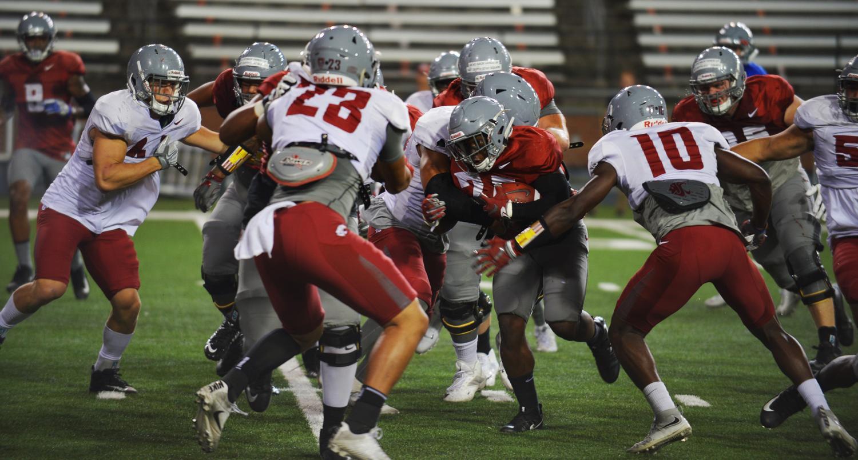 WSU players pile around the football Saturday night  at Martin Stadium.