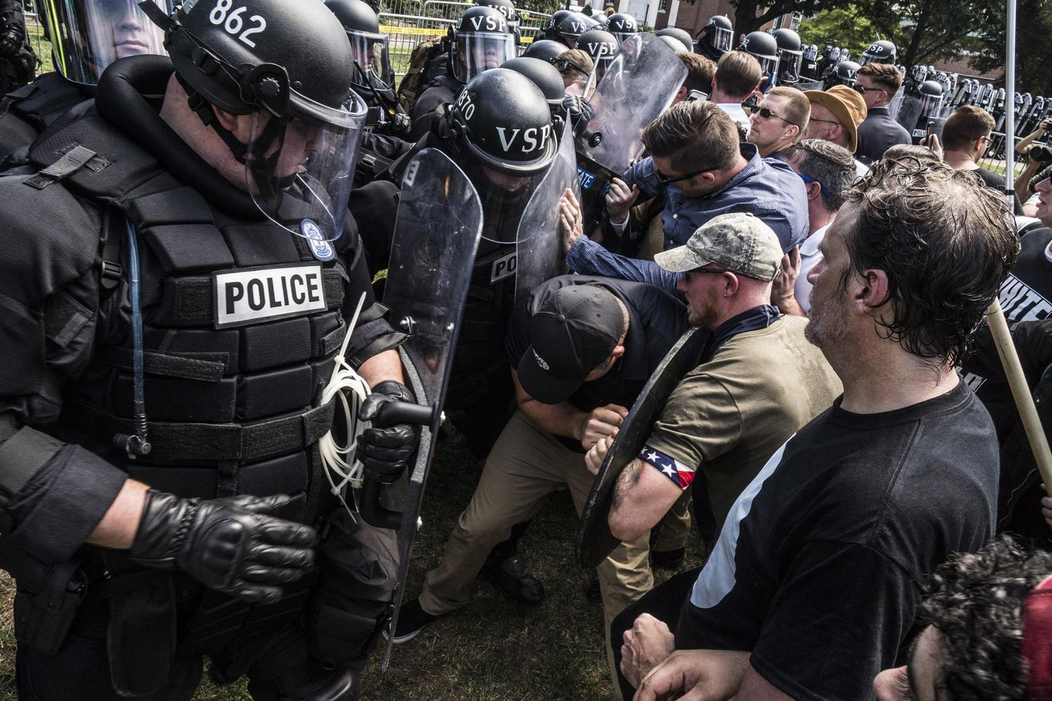 Riot police and alt-right rally members clash on Saturday Aug. 12, 2017 in Lee Park in Charlottesville, Va.