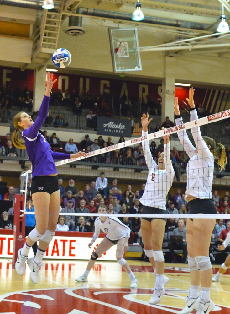 UW freshman middle blocker Lauren Sanders tries tipping the ball over Cougar blockers.