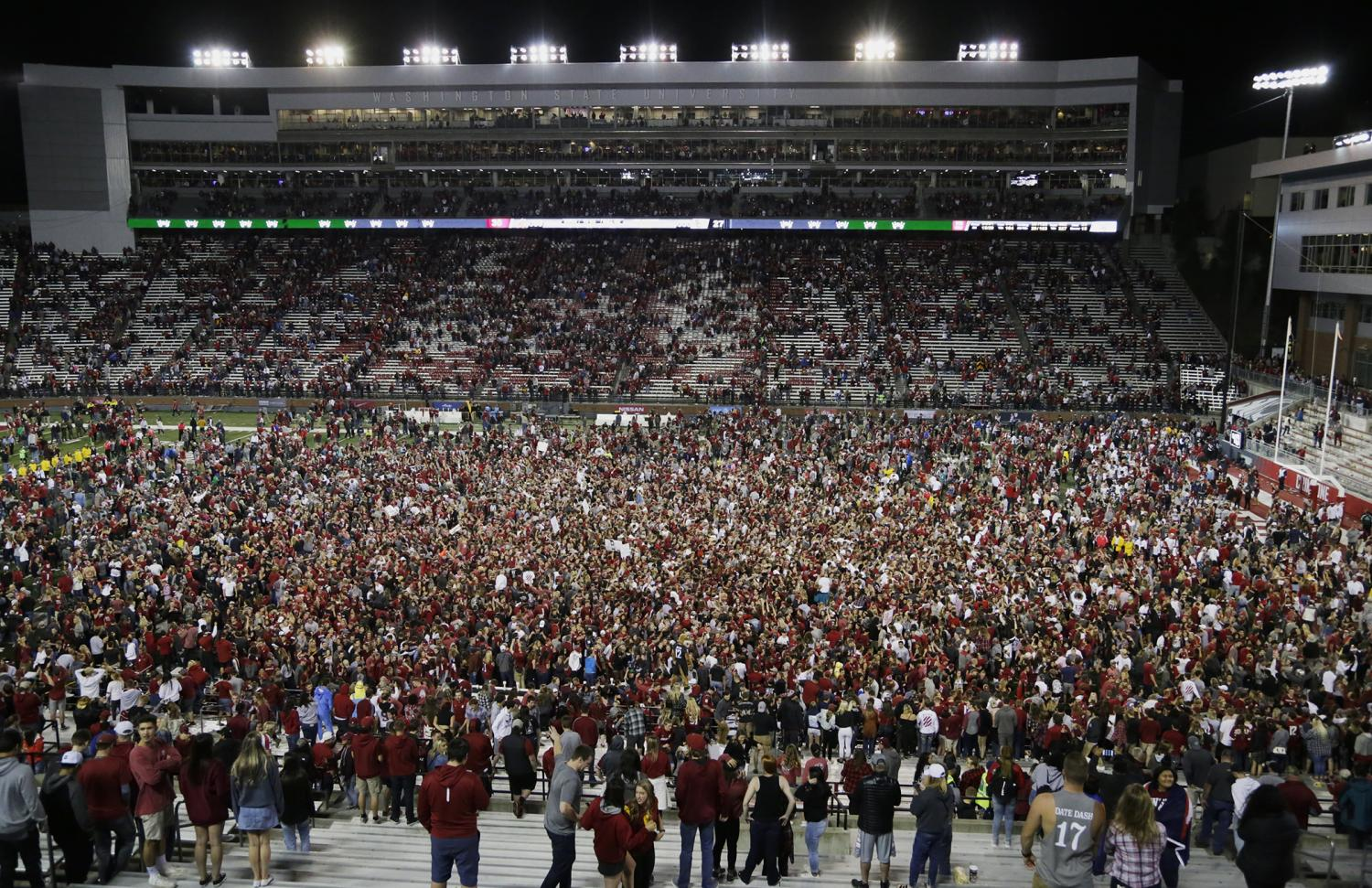 WSU fans storm the field after the team's 30-27 win over USC on Friday at Martin Stadium.