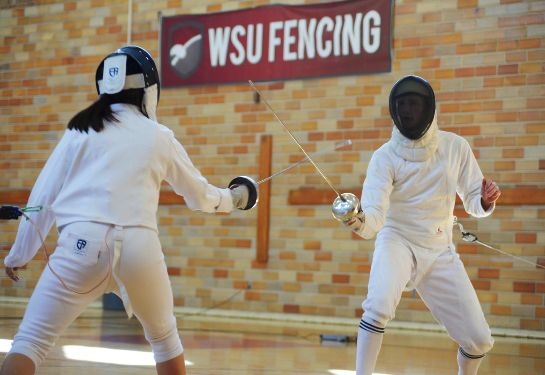Fencing Club members Nancy Fu, left, and Garrett Van Beek practice epee style Sunday in Smith Gym, Room 117.