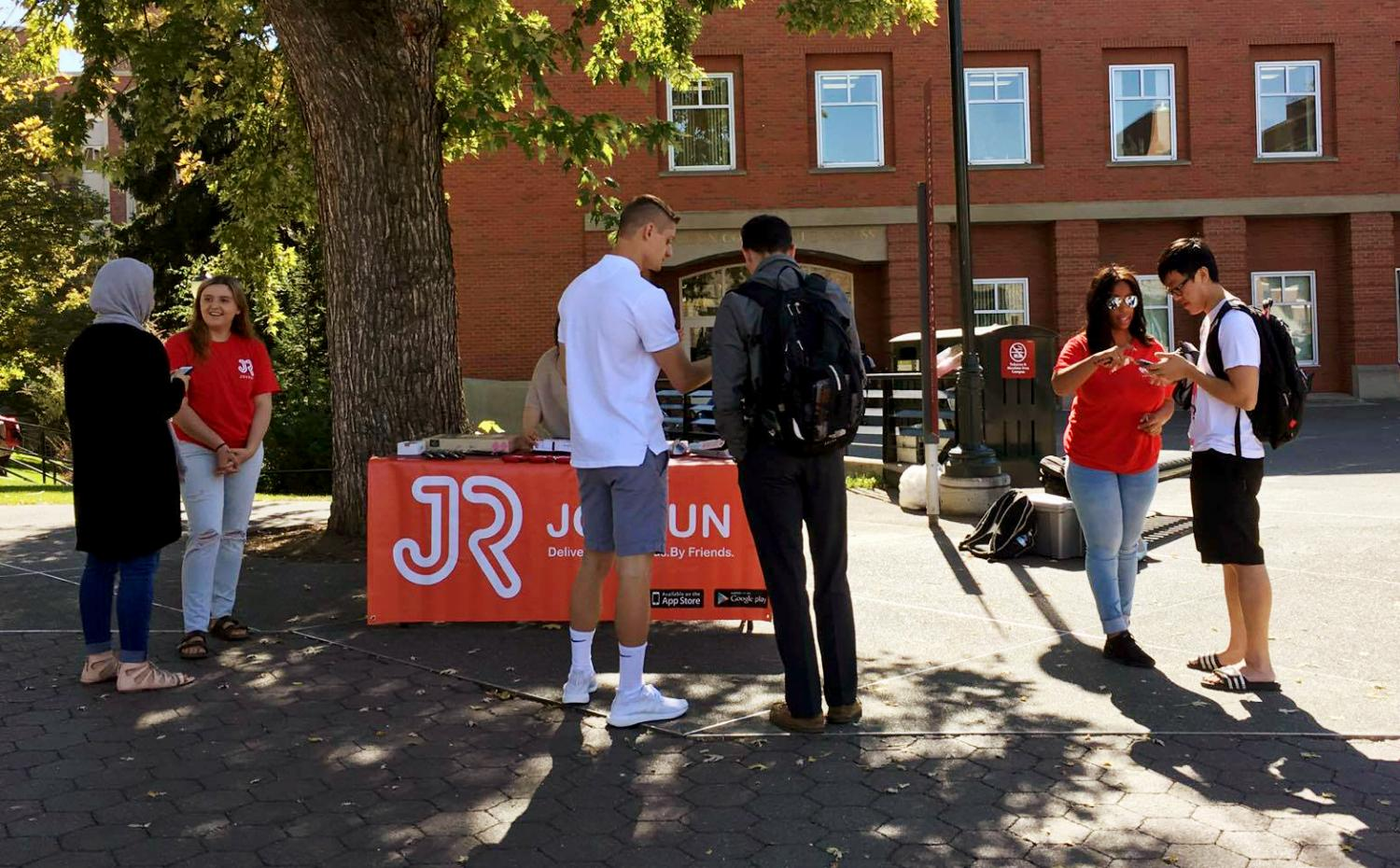 Student interns speak with people passing by on the Glenn Terrell Friendship Mall, offering free food, such as pizza and donuts, to those who sign up on the app.