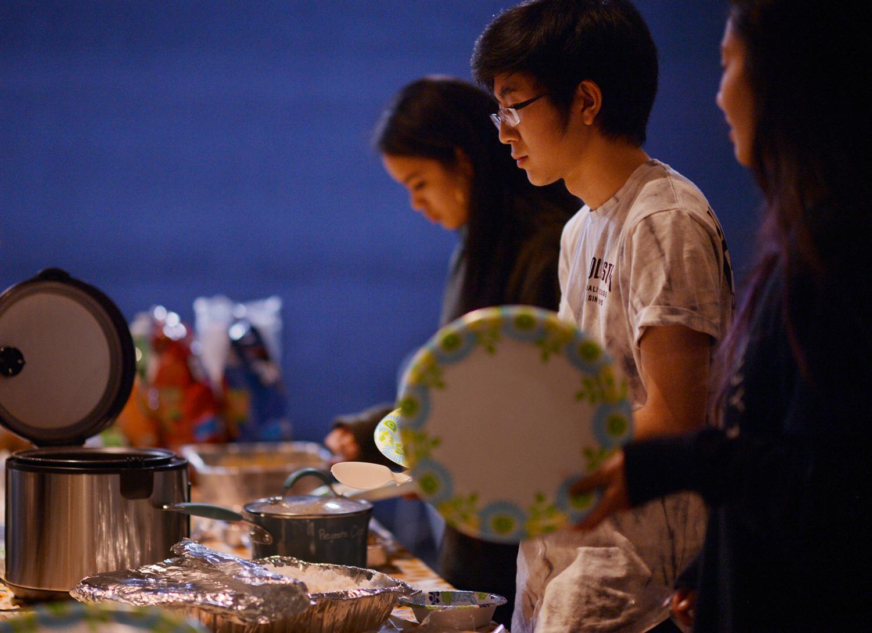 Freshman Dayton Matsushima fills his plate at a Friendsgiving dinner last week.