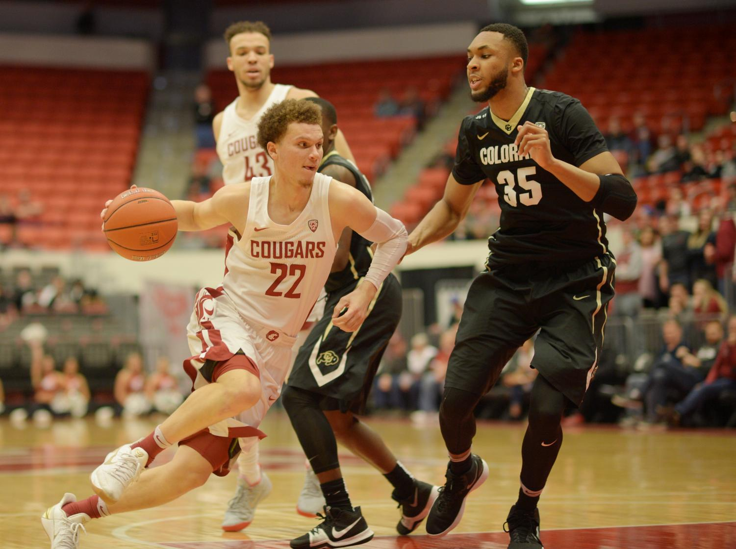 Sophomore guard Malachi Flynn dribbles around Colorado freshman center Dallas Walton in a game  Feb. 15 at Beasley Coliseum. WSU won 73-69 to snap a seven-game losing streak.