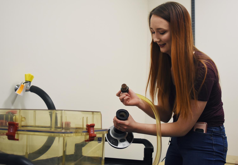 Joanne Kunze, a senior neuroscience major, demonstrates how she used a vaporizer to intoxicate rats and study how marijuana affects hormones involved in feeding behavior.