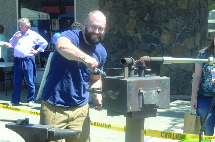 Elijah Williams, the head blacksmith of Fire Creek Forge, creates knives and razors at the Moscow Farmers Market on Saturday.