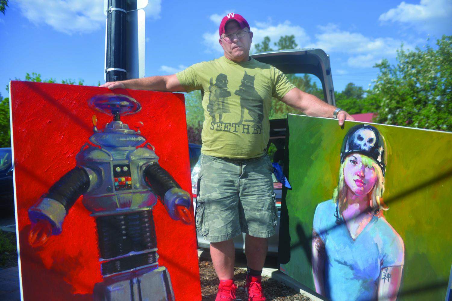 Henry Stinson, a local artist who has a painting studio in Pullman, holds some of his oil on canvas paintings that will be featured at the Neill Public Library during the ArtWalk.