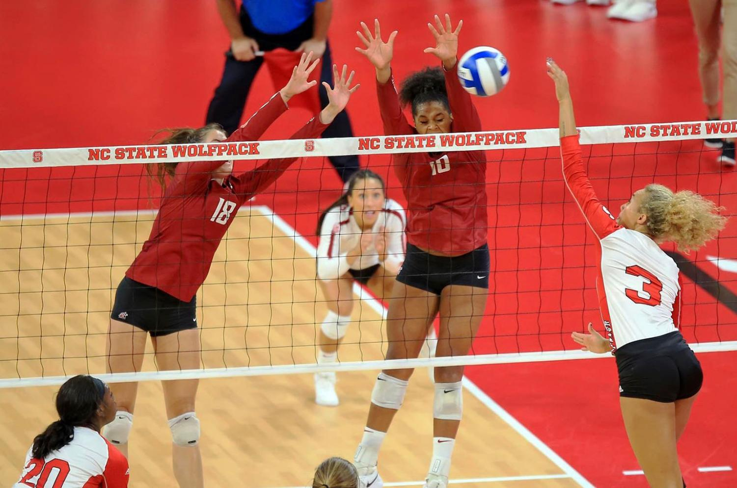 Senior middle blocker Ella Lajos, left, and senior outside hitter Taylor Mims, middle, jump to block a hit made by North Carolina sophomore opposite Melissa Evans on Aug. 26 in Reynolds Coliseum.