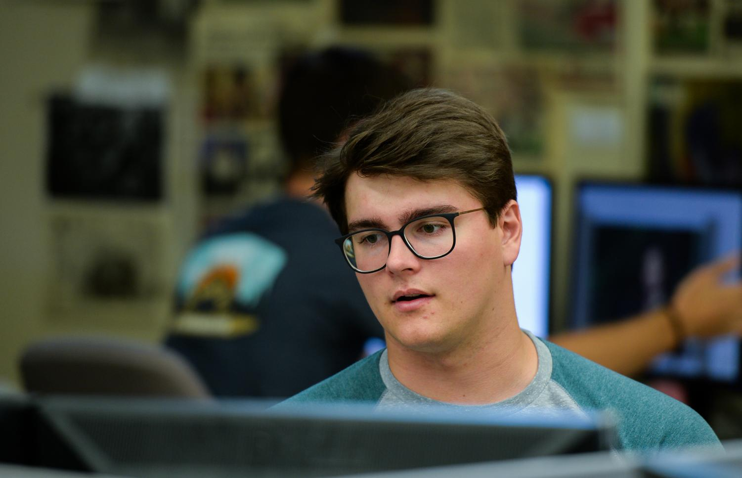 Evergreen Opinion Editor Luke Hudson reads out a column during production Tuesday night in the newsroom.