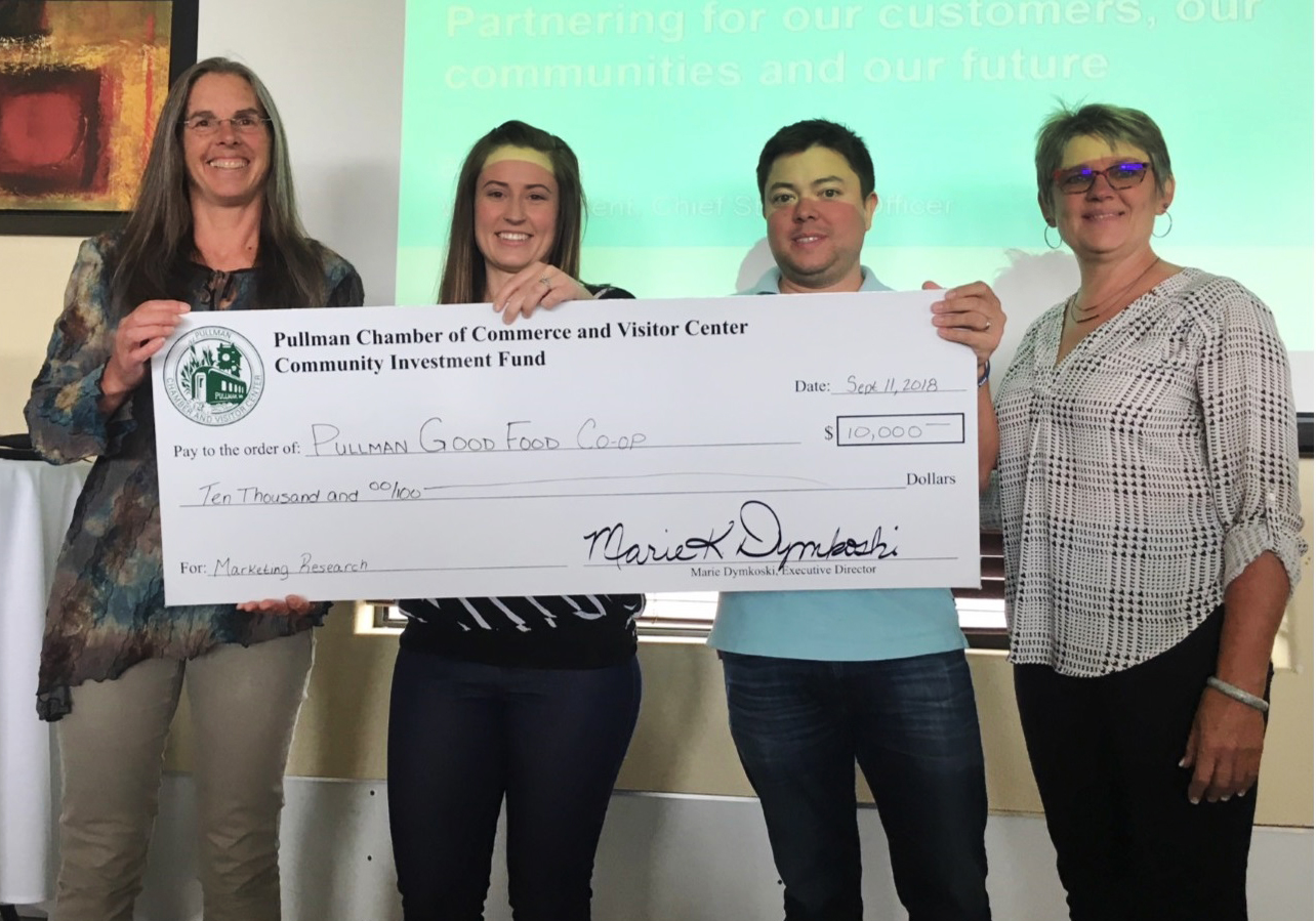 Co-op President Destiny Sternod, second from left, and Tony Poston, Pullman Chamber and Visitor Center board president, second from right, hold their $10,000 check with other co-op supporters.