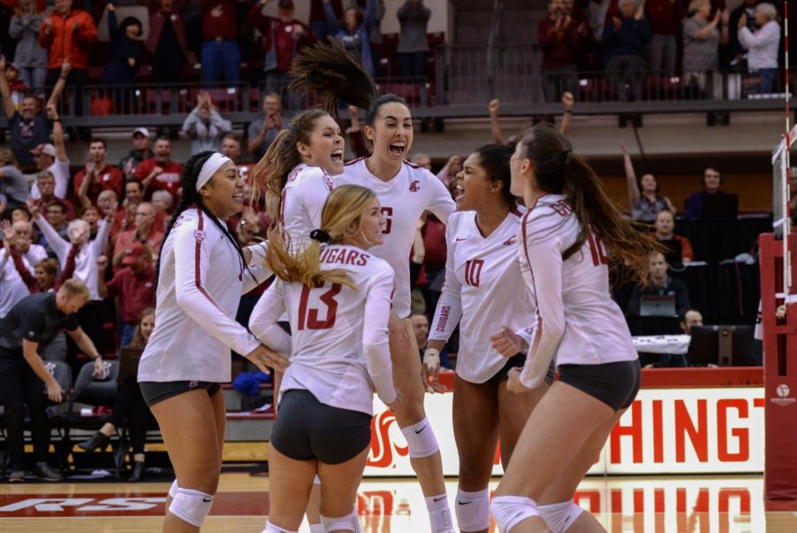 The WSU womens volleyball team celebrates on-court after scoring the 18th and winning point against Utah on Friday night in Bohler Gym.
