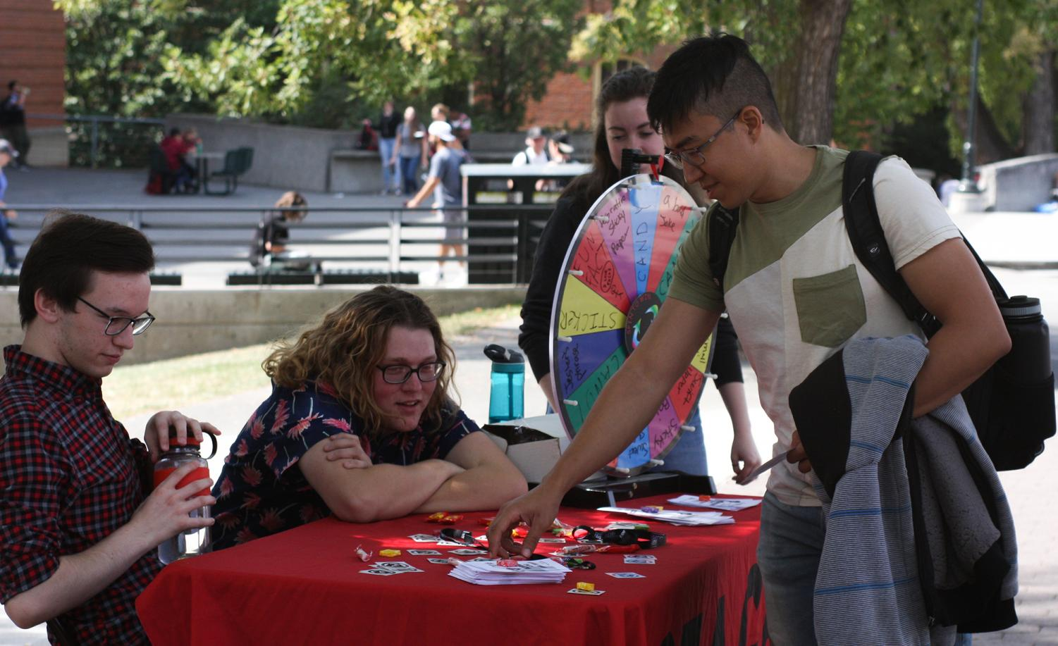 Chemical engineering major Elyas Alnamnakani picks up a flyer for STAGE Student Theatre's improv comedy show at Glenn Terrell Mall on Wednesday.