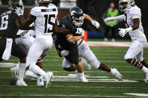 Freshman running back Max Borghi attempts to break through Oregon defense in order to gain yards during the game against Oregon Saturday at Martin Stadium.