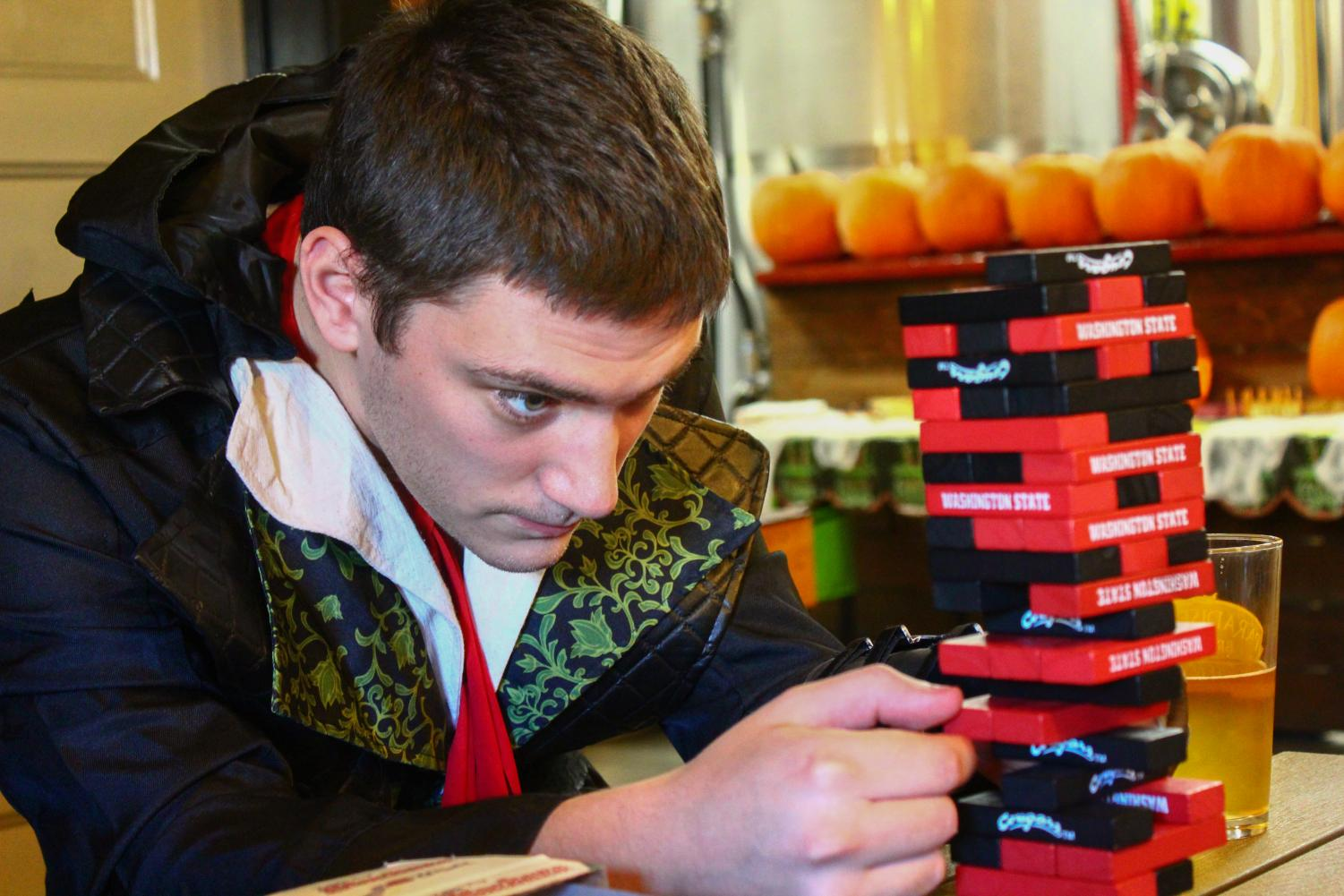"Zachary Brown, a fifth-year senior double majoring in Asian studies and Chinese language, plays a mini set of Jenga at the Paradise Creek ""Booery"" Halloween Party at the brewery's Trailside Taproom on Saturday afternoon."