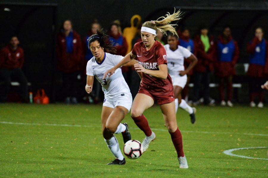 Junior forward Morgan Weaver dribbles the ball downfield as she attempts to keep it away from University of Washington sophomore defender Kaylene Pang on Friday at the Lower Soccer Field.