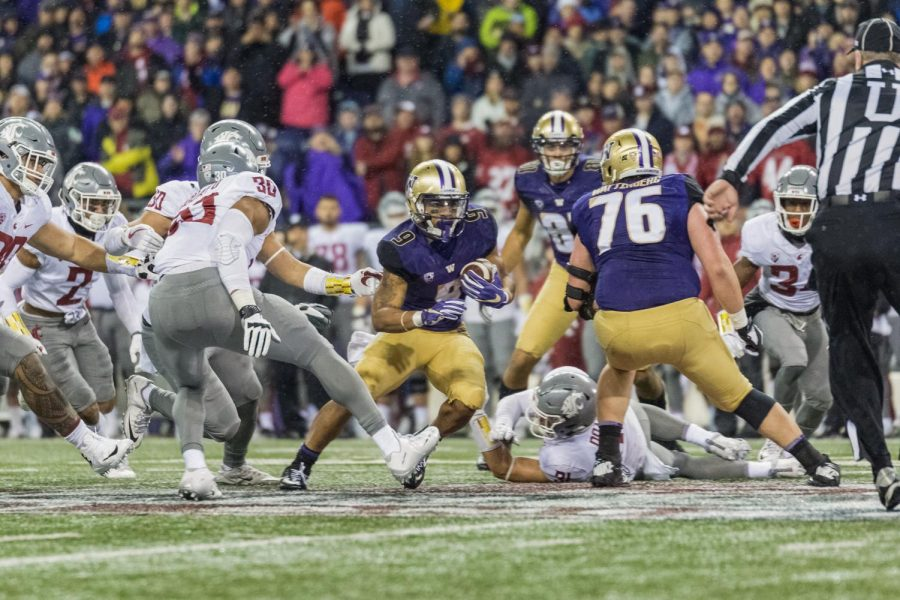 Myles+Gaskin+breaks+through+the+WSU+defense+during+the+2017+Apple+Cup.