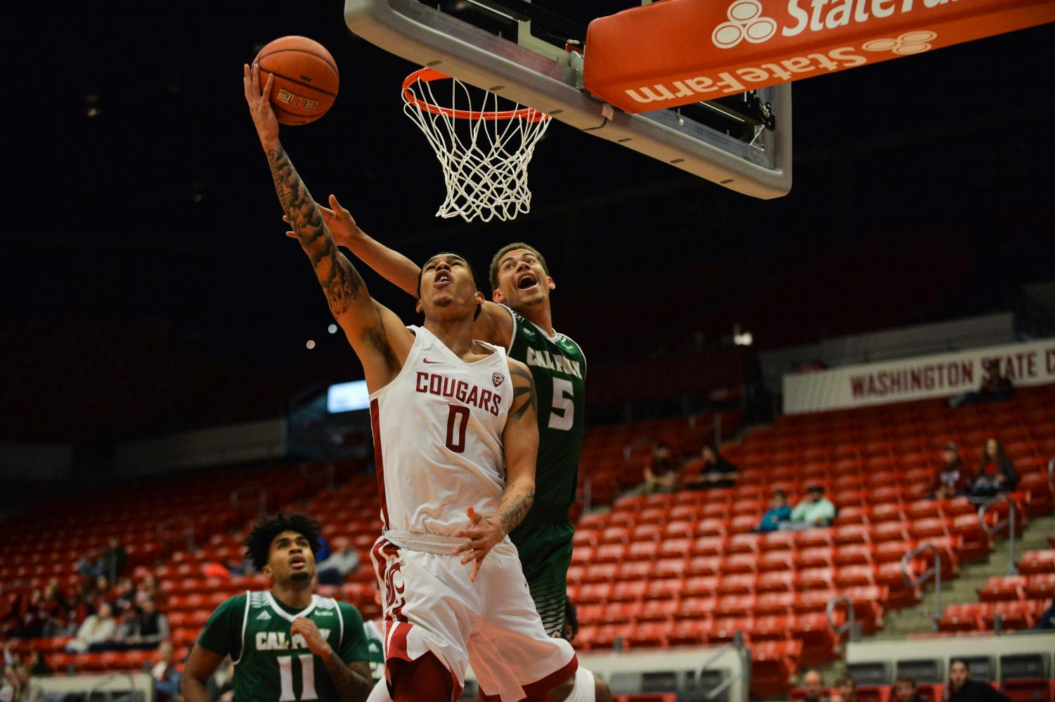 Junior power forward Isaiah Wade shoots a layup past Cal Poly sophomore wing Mark Crowe during the Cougars' 84-70 win over the Mustangs on Nov. 19 in Beasley Coliseum.