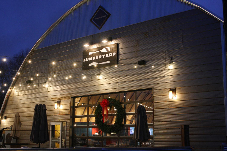 The newly-opened Lumberyard Food Hall lights up its outside patio Sunday evening.