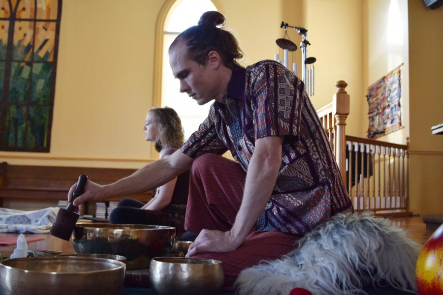 Matthew Hardens, maintenance worker and creator of a boutique for shirts from Indonesia, uses a bowl's sound to help guide a meditation session Jan. 12 in the Unitarian Universalist Church of the Palouse.