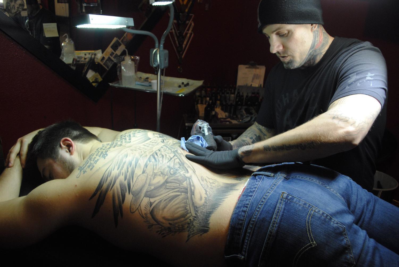 Chris Peltier, owner of Blood Diamond Ink, works on back piece for mechanical engineering major Tyler Manix.