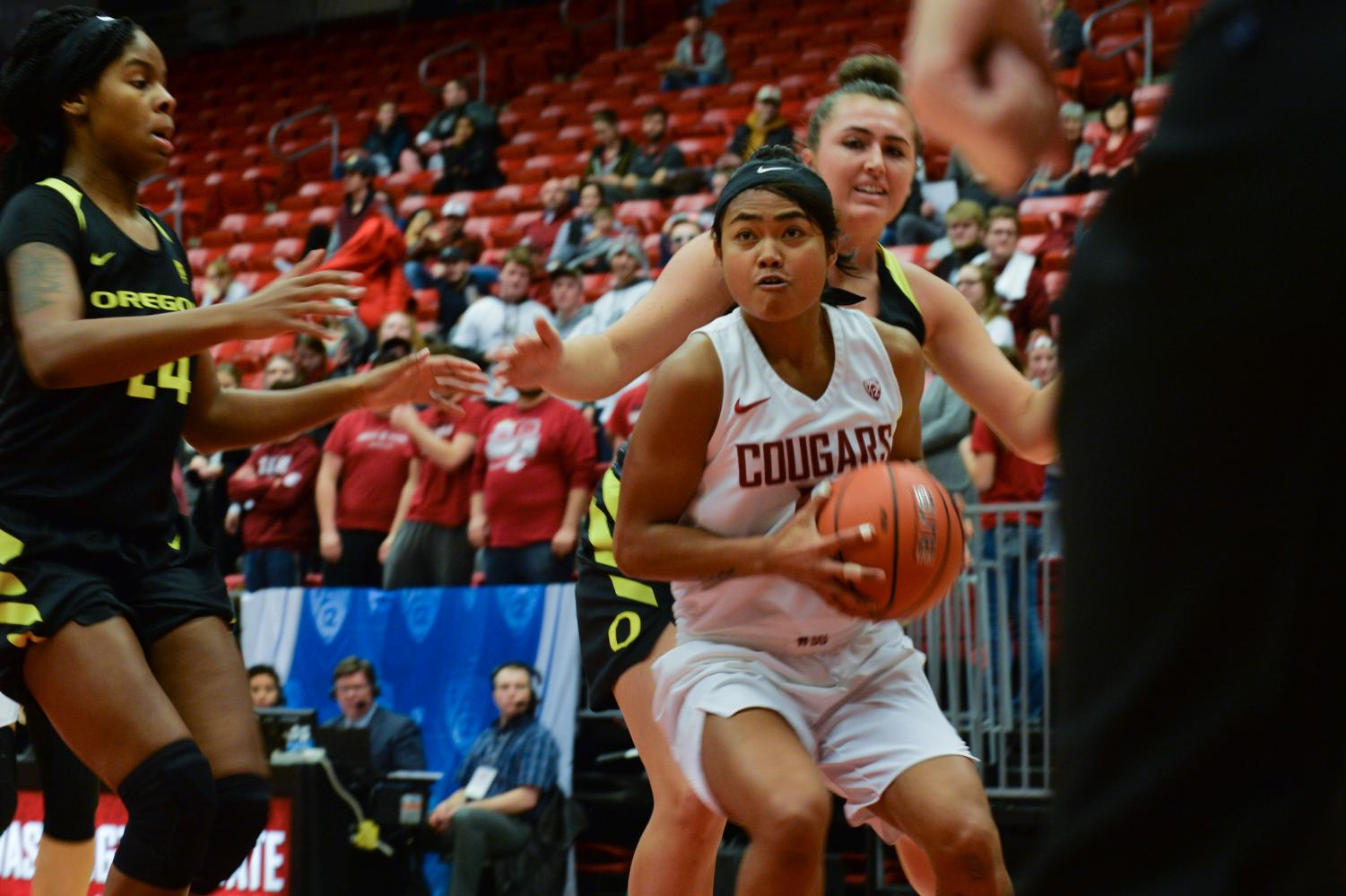 WSU junior guard, Chanelle Molina, center, looks toward the basket as she is approached by Oregon junior forward, Ruthy Hebard, left, U of O red-shirt sophomore forward, Erin Boley, during the game on Friday night at Beasley Coliseum. Cougs lost 64-79.
