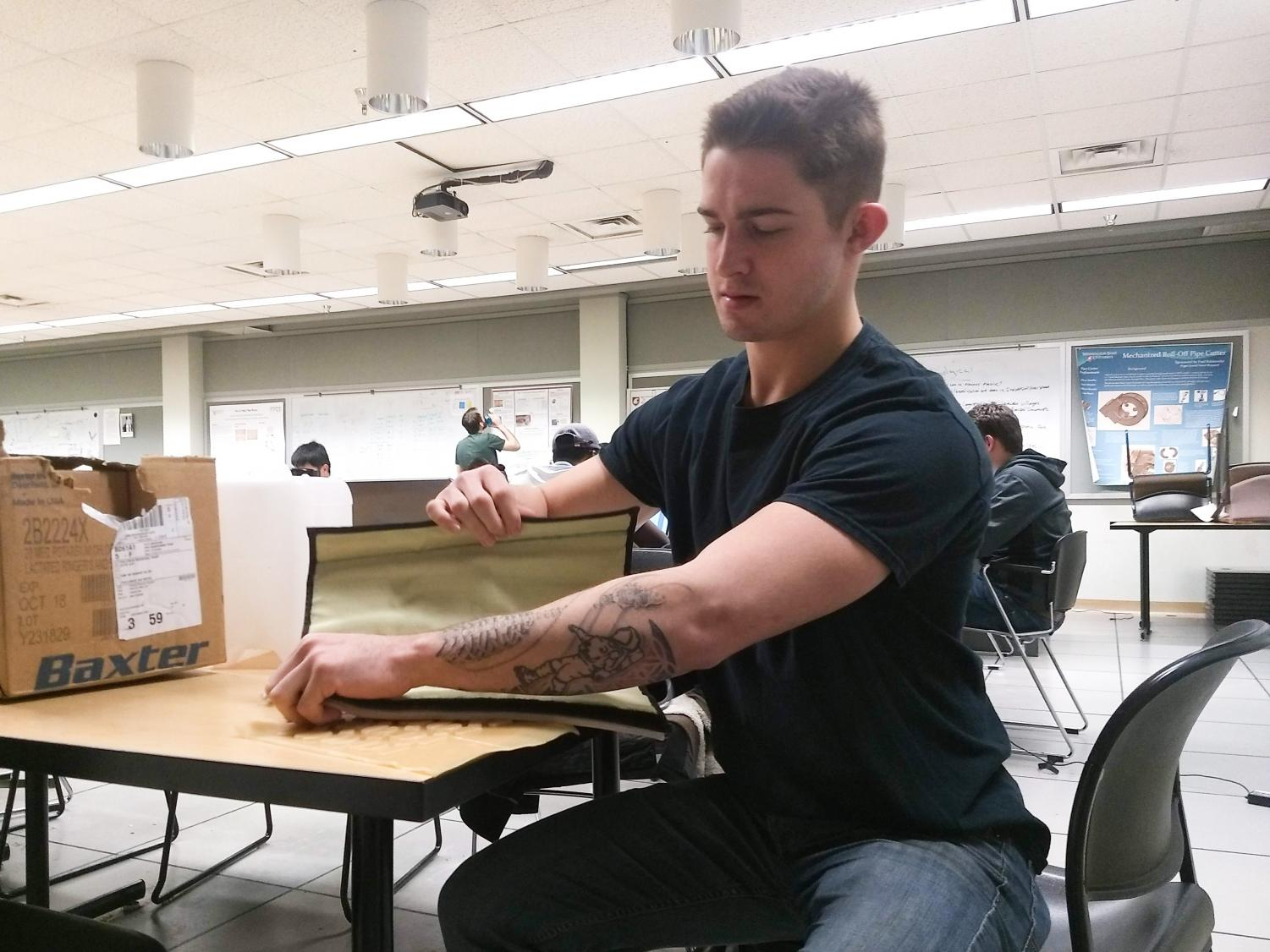 Mechanical engineering senior Zac Cannon adjusts the vein tubes on the simulated IV arm. The purpose of the arm is to help healthcare providers practice the technical aspects of finding the vein, while simultaneously practicing social skills.
