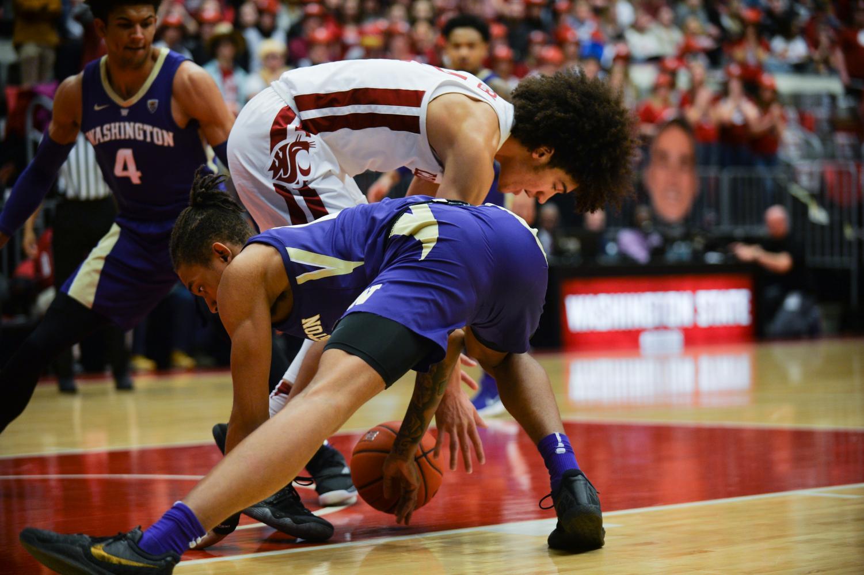 WSU freshman forward CJ Elleby battles a UW defender for the ball Saturday against Washington at Beasley Coliseum.