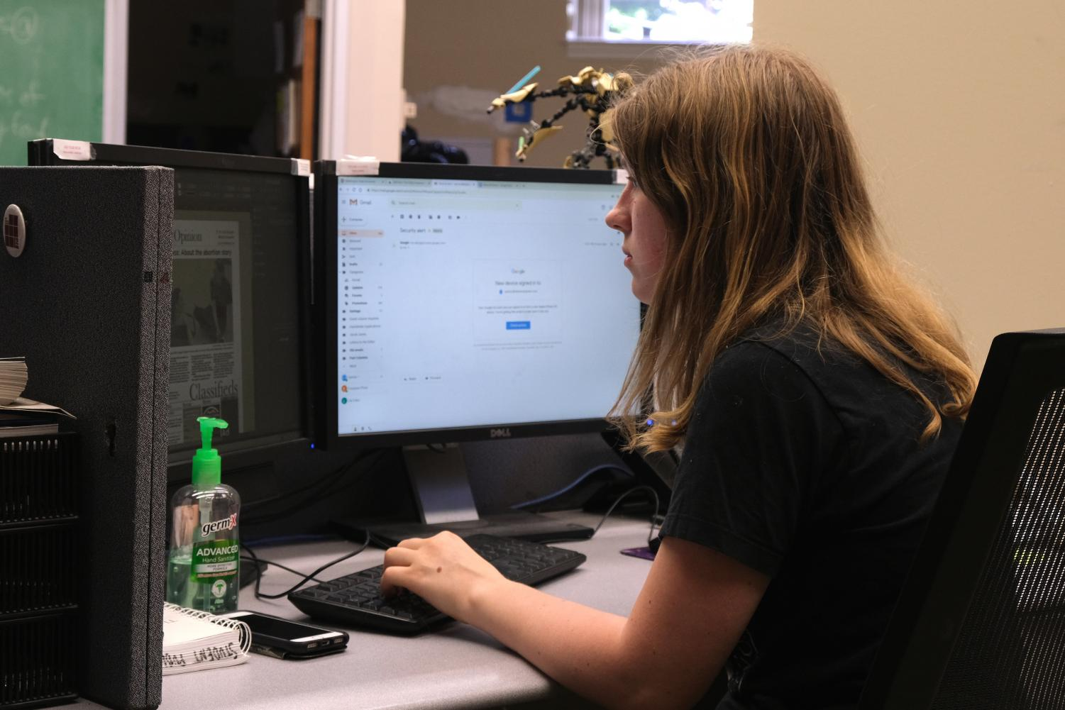 Alana Lackner, Opinion Editor for The Summer Evergreen, previews this week's Opinion section at her desk Wednesday evening in Murrow Hall.