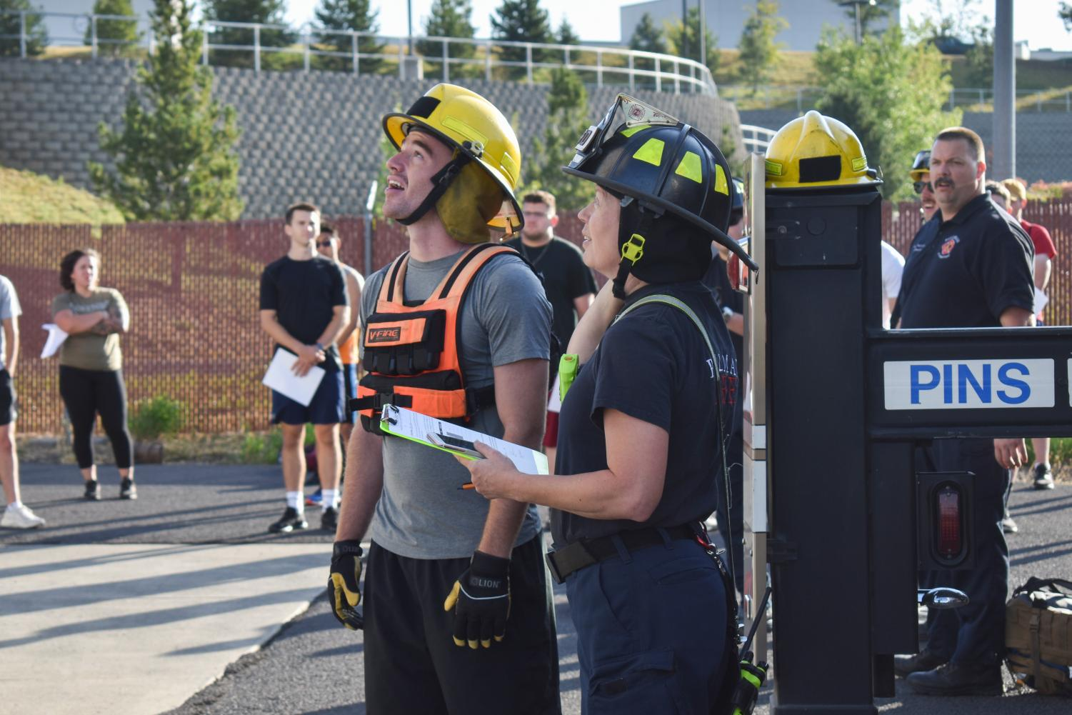 WSU sophomore Nathan Richardson and Pullman Firefighter Angela Teal look at the firefighter training tower while other participants wait for their turn at the facility Saturday morning.