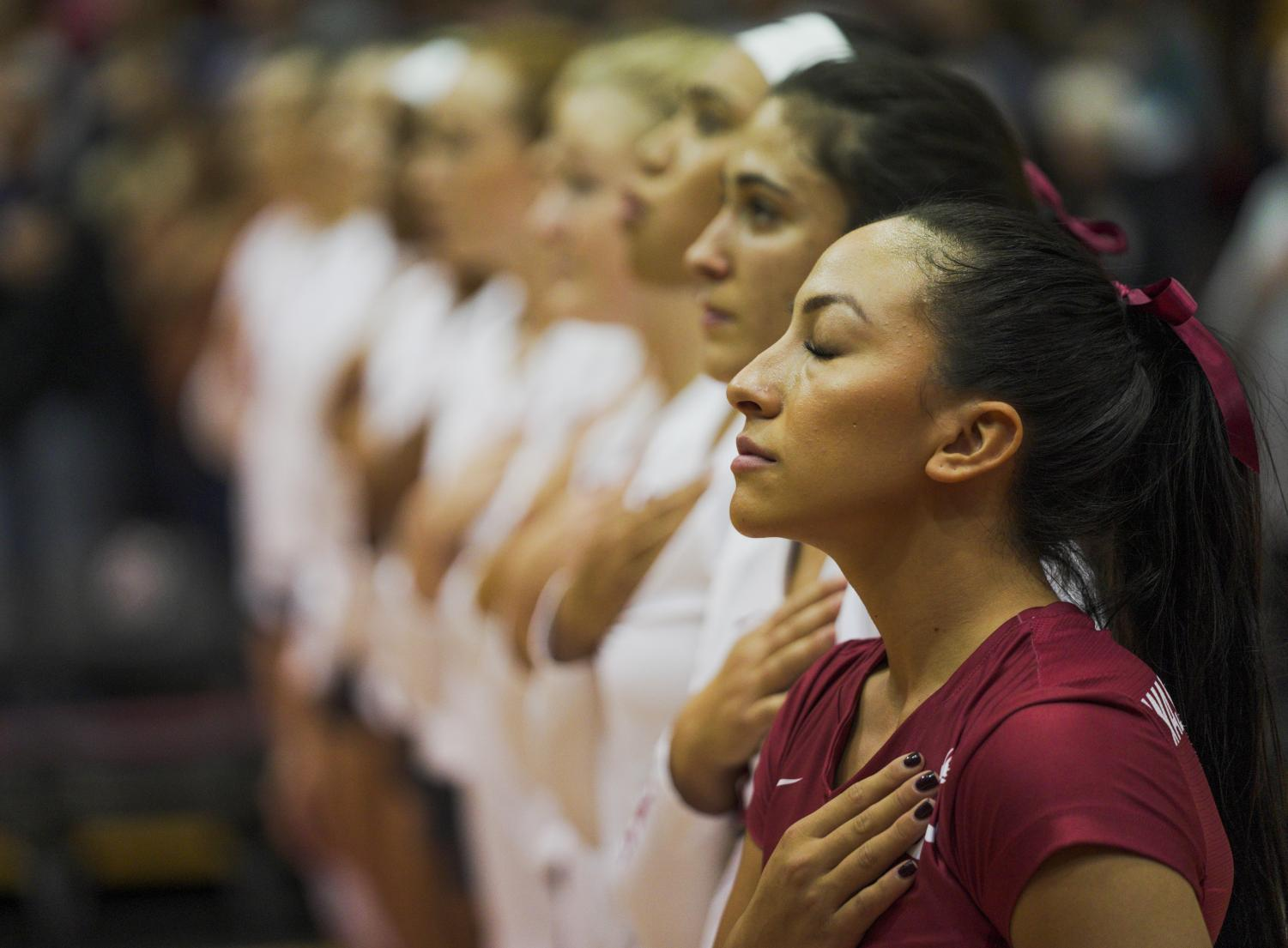 Alexis Dirige stands with her team as the WSU band plays the national anthem before the Cougars upset the University of Washington Huskies on Sept. 25 at Bohler Gym.