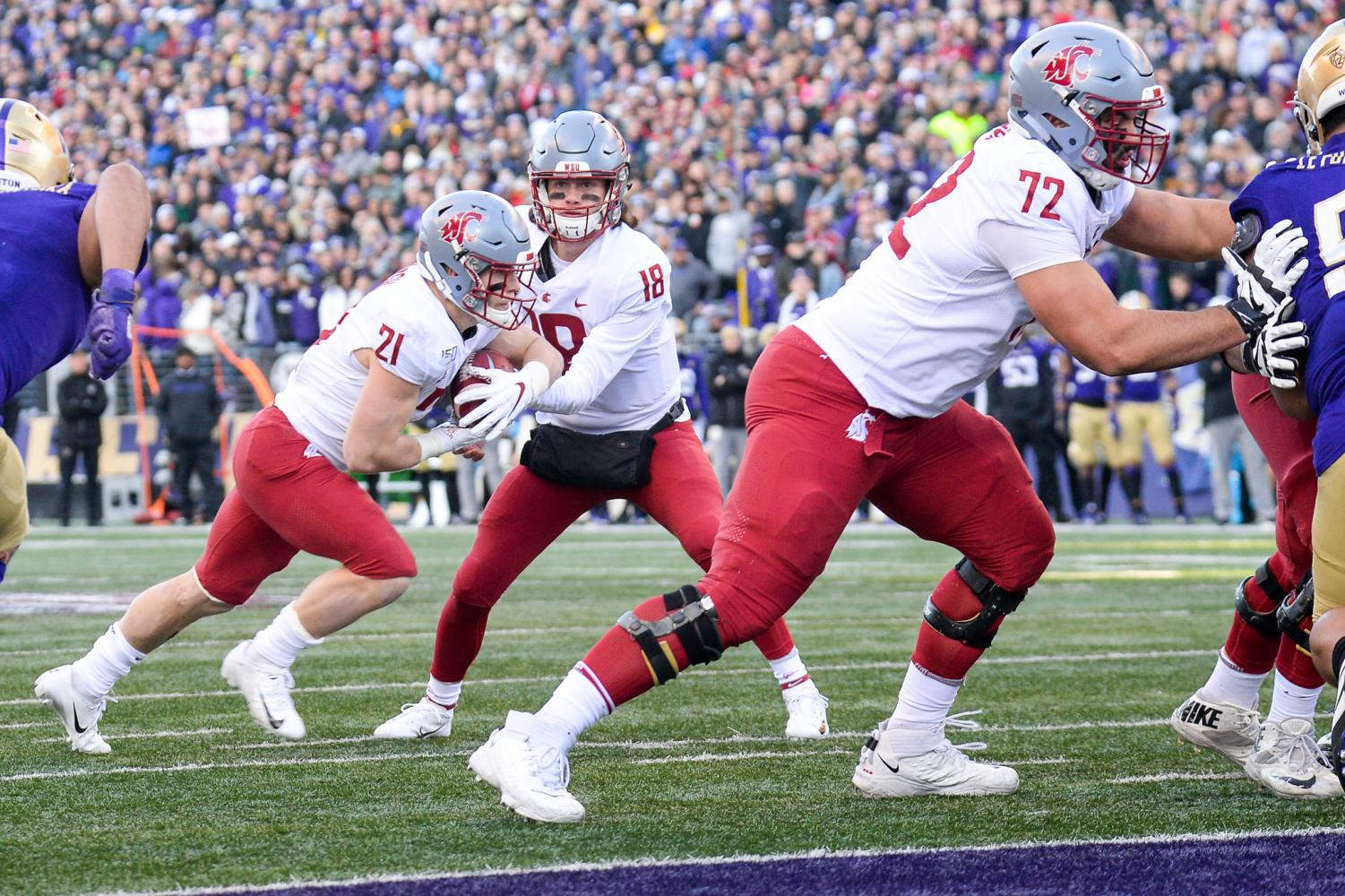 Senior quarterback Anthony Gordon hands the ball off to Sophomore running back Max Borghi who scores the first touchdown of the Apple Cup Friday afternoon at Husky Stadium.