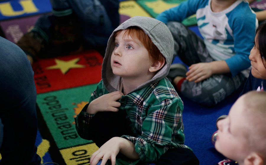 4-year-old Zeddicus Jones looks up as Becki McFarland, suns p.m. lead teacher, reads a book to the class on Thursday at Community Child Care Center.