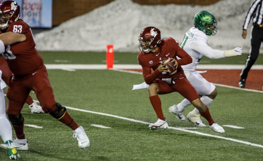 Freshman quarterback Jayden de Laura evades an Oregon defender and looks to complete the play Saturday night in Martin Stadium.
