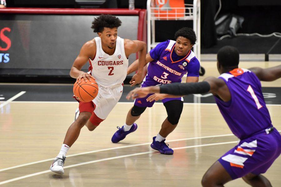 Junior guard Myles Warren dribbles past a Northwestern defender towards the basket.