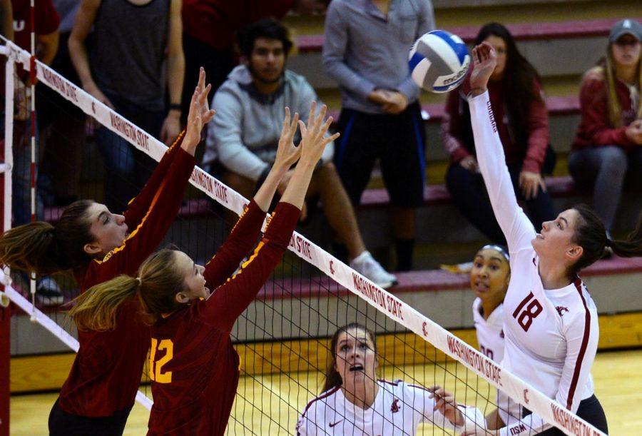 Freshman middle blocker Jasmine Martin rises up for spike over defender.