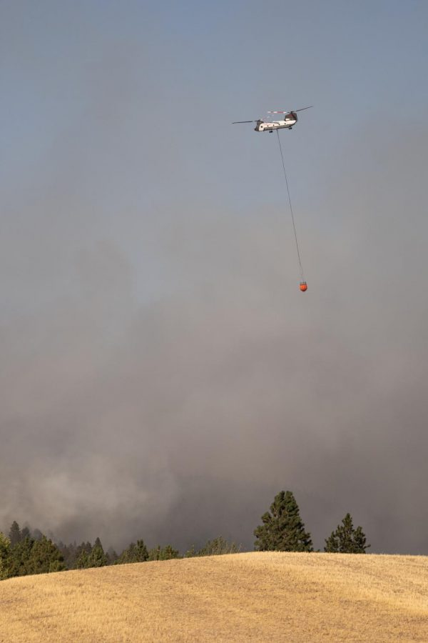 An aerial firefighter crew prepares to drop water over the fire.