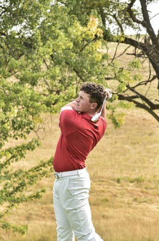 WSU golfer Max Sekulic swings away on a golf course.