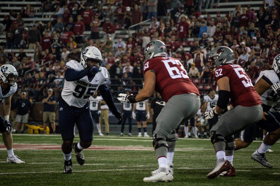 Washington State University offensive linemen, Liam Ryan and Jarrett Kingston, push back Utah State defensive players at Martin Stadium in Pullman, Wash., Saturday, Sept. 4, 2021.