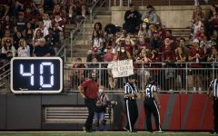 WSU Head Coach Nick Rolovich walks to the sideline as a fan holds a sign at him Sept. 4 at Martin Stadium in Pullman.