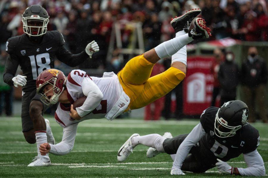 Washington State University defensive back Jaylen Watson (0) trips University of Southern California quarterback Jaxson Dart (2) during the first half of a college football game, Saturday, Sept. 18, 2021, in Pullman, WA.