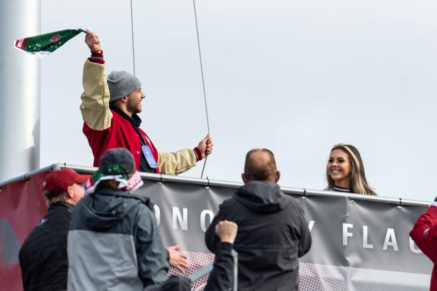 Washington State University alumni and quarterback Anthony Gordon raises the WSU flag before a football game at Martin Stadium, Saturday, Oct. 23, 2021, in Pullman, Wash.